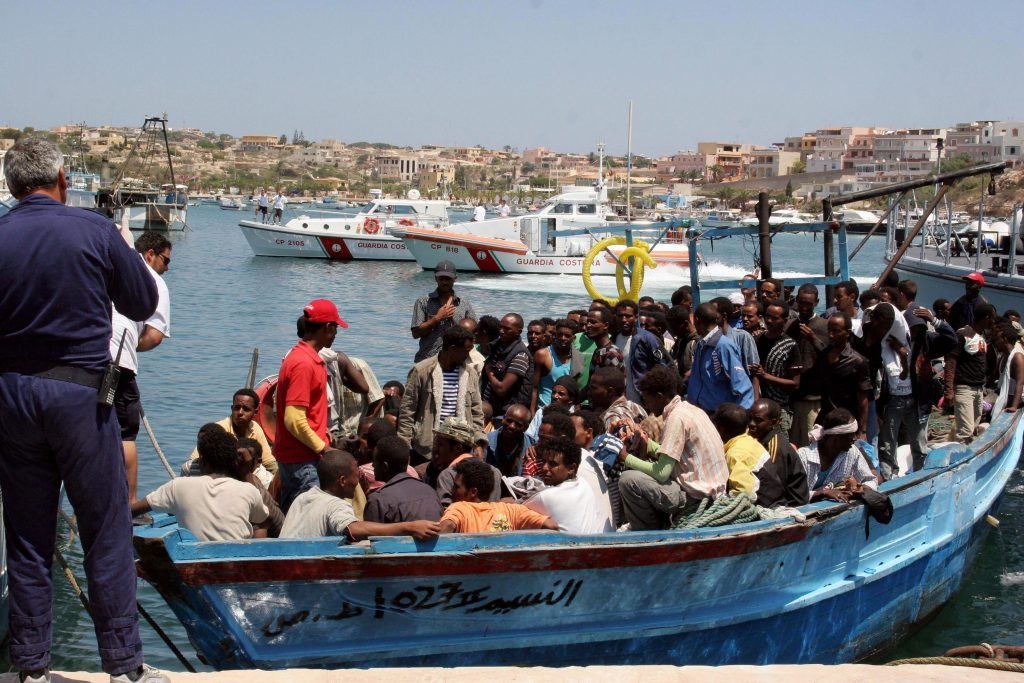 Would-be immigrants arrive on a boat in the port of Italy's southern island of Lampedusa late on July 31, 2008. Italy's coast guard intercepted around 800 illegal immigrants on five boats off the island of Lampedusa on July 31. One boat, carrying 339 people, including 47 women and four children, got as far as the Sicilian island's port. The reception centre on Lampedusa, which can hold 700 immigrants, was overwhelmed by the scale of new arrivals after some 400 illegal immigrants turned up on the island. AFP PHOTO / Mauro Seminara (Photo credit should read Mauro Seminara/AFP/Getty Images)